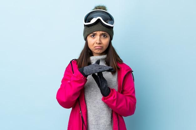 De gemengde vrouw van de rasskiër met snowboarding glazen over geïsoleerde blauwe ruimte die tijd uit gebaar maken