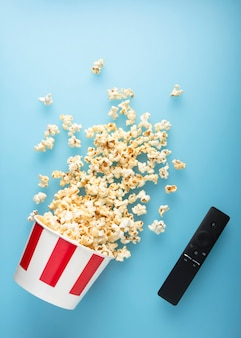 De gemorste popcorn op een blauwe achtergrond met tv verwijdert.