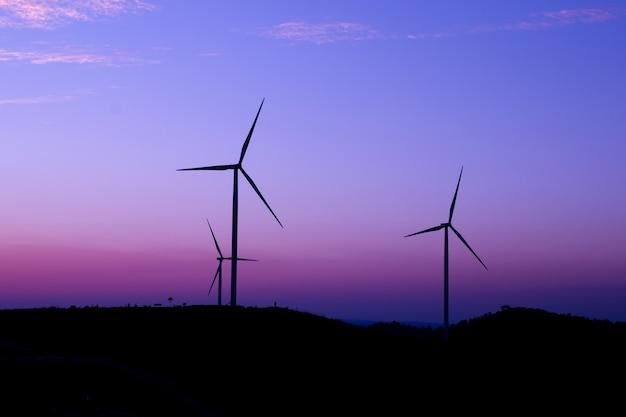 De generator van de windturbine tegen een dramatische de schemeringtijd van de zonsonderganghemel.