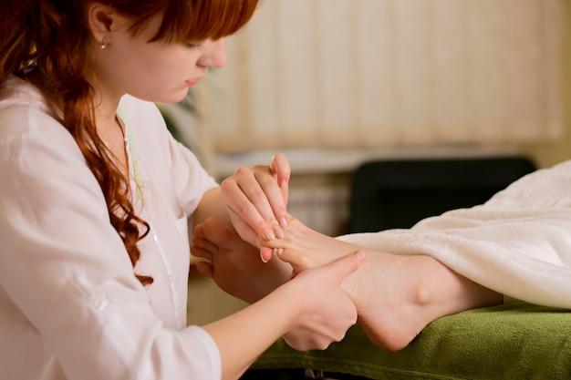 De genezer reinigt de voeten van de patiënt energetisch Premium Foto