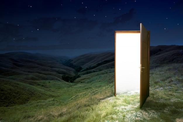 De geopende deur op de top van groene heuvels
