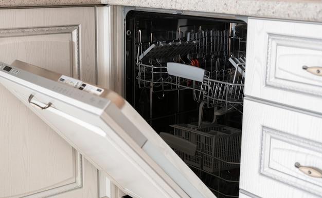 De geopende nieuwe lege vaatwasser machine in de keuken