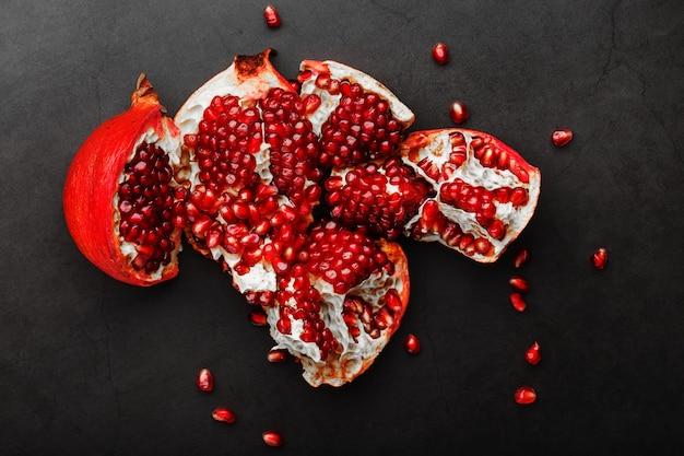 De geopende vruchten van een rijpe open granaatappel liggen.