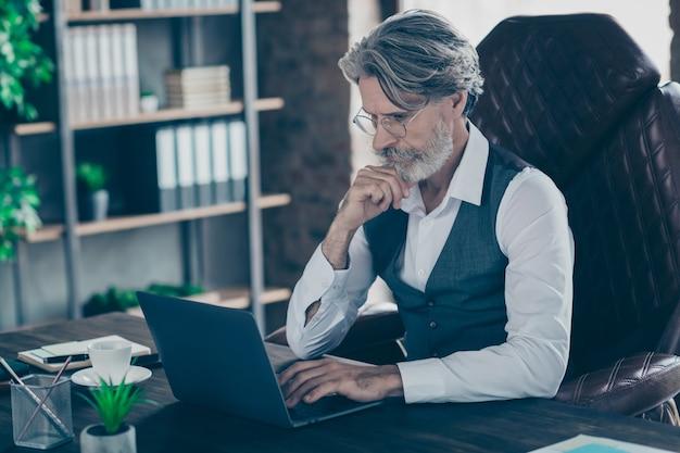 De gerichte zakenman zit stoel die website op laptop in bureau zoekt