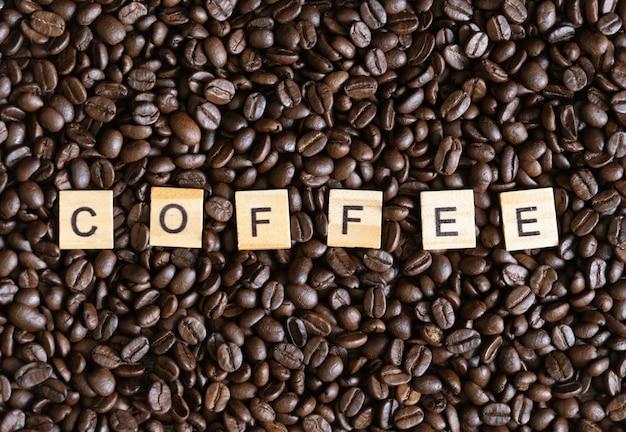 De geroosterde achtergrond van arabicakoffiebonen op houten lijst.