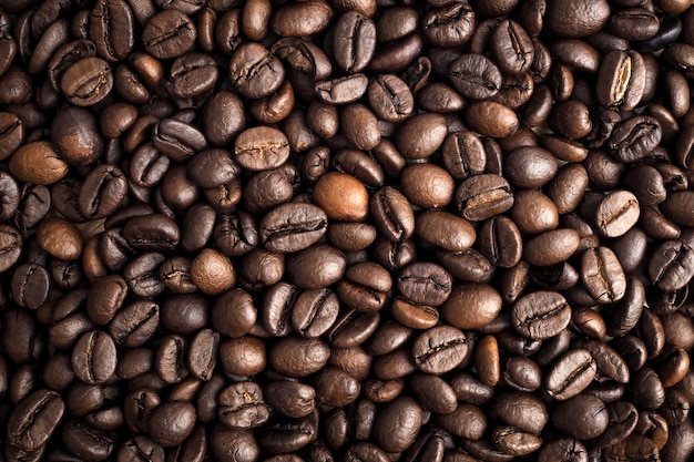 De geroosterde die textuur van koffiebonen als achtergrond wordt gebruikt