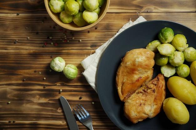 De geroosterde kip met aardappels en spruit van brussel diende op zwarte plaat op houten lijst