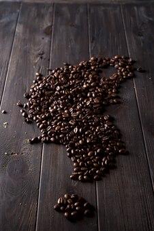 De geroosterde koffiebonen, kunnen op een houten donkere achtergrond worden gebruikt