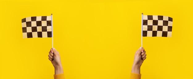 De geruite vlag overhandigt binnen gele achtergrond, panoramisch beeld