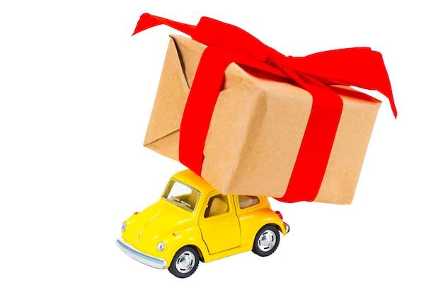 De geschenkdoos op speelgoed retro auto op witte achtergrond. kerst vakantie viering concep.