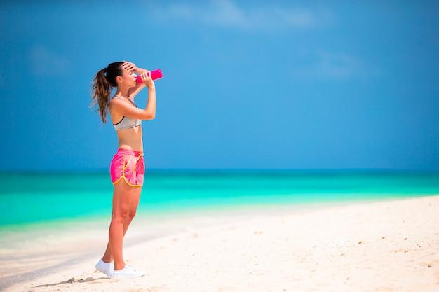 De geschikte jonge vrouw drinkt water op wit strand