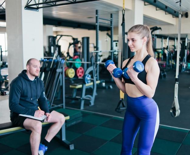 De geschiktheidsinstructeur houdt toezicht op en noteert in notitieboekjeresultaten van opleiding van jonge atletische blonde die oefeningen met domoren in haar handen bij gymnastiek uitvoeren