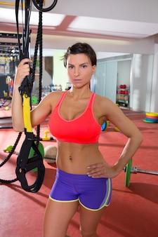 De geschiktheidsvrouw die van crossfit zich bij trx van de gymnastiekholding bevindt