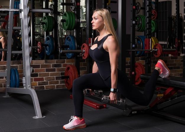 De geschiktheidsvrouw het doen valt hurkende oefening met doos in gymnastiek uit