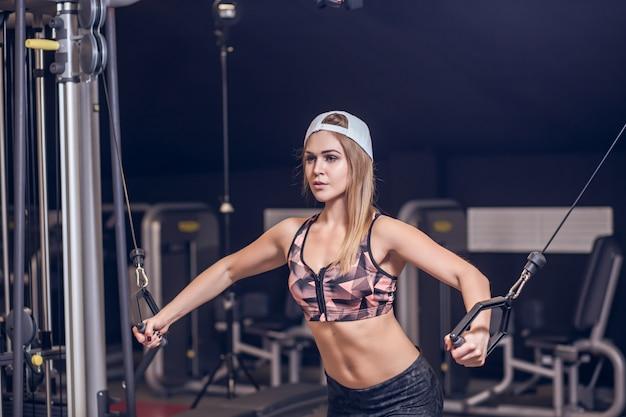 De geschiktheidsvrouw voert oefening met oefeningsmachine uit kabeloversteekplaats in gymnastiek