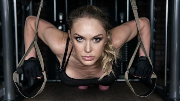 De geschiktheidsvrouw voert opdrukoefeningen op ophangingslussen in de gymnastiek uit
