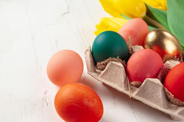 De geschilderde paaseieren in een eggbox met verse tulpen sluiten omhoog