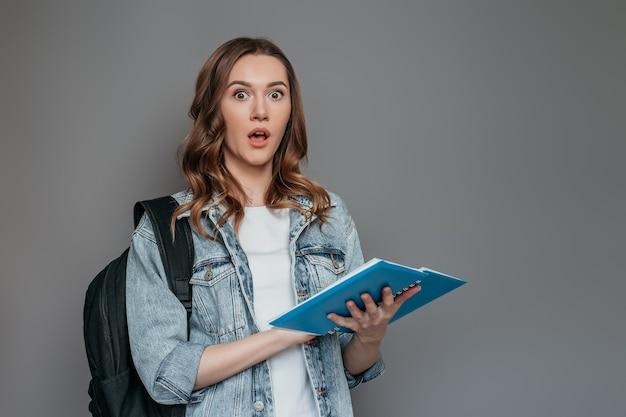 De geschokte kaukasische brunette van de studente leert examen en leest notitieboekje dat op grijze muur wordt geïsoleerd. kopieer ruimte