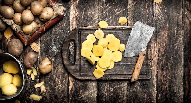 De gesneden aardappelen op een oude houten plank Premium Foto