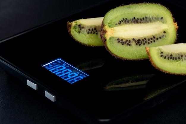 De gesneden kiwi is op een elektronische weegschaal op een zwarte achtergrond.