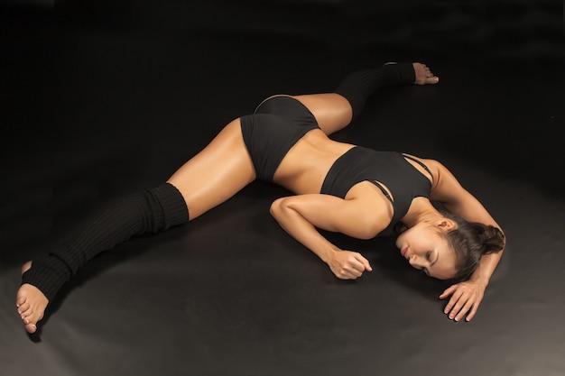 De gespierde jonge vrouw atleet zittend op de splitsing op zwarte achtergrond.