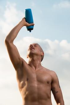 De gespierde man schuilt water op zich om af te koelen