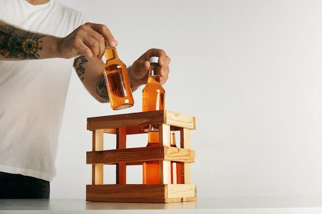 De getatoeëerde man dient in lege witte t-shirt flessen met cider in een houten kist te zetten die op wit wordt geïsoleerd