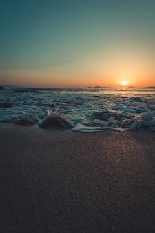 De getijden spatten tegen het zand