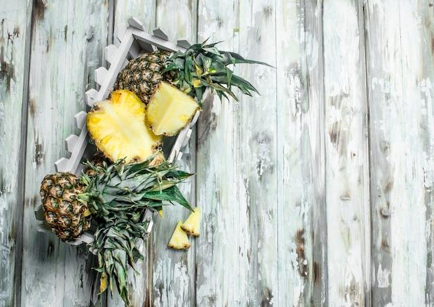 De geur van verse ananas per doos. op wit houten oppervlak