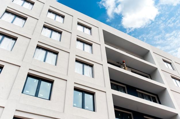 De gevel van het huis in aanbouw met een balkon en kleurrijke sierpleister
