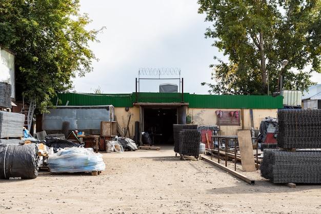 De gevel van het metalen magazijn, een commercieel gebouw met ingangen voor auto's voor het opslaan van goederen