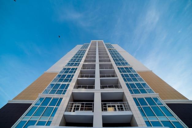 De gevel van het nieuwe gebouw met balkons tegen een blauwe lucht met wolken is van onder naar boven verwijderd