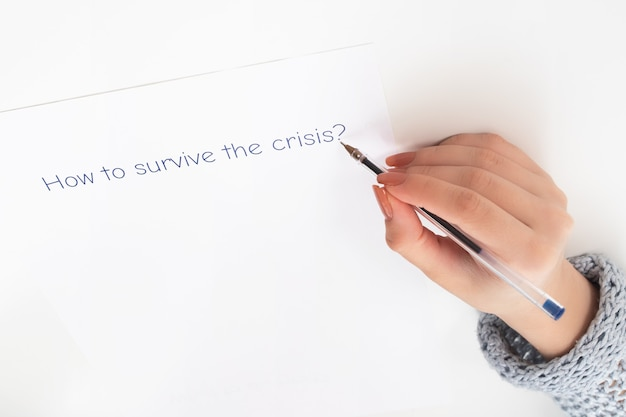 De gevolgen van de pandemie van het coronavirus. vrouwelijke handen schrijven op een stuk papier hoe ze de crisis kunnen overleven