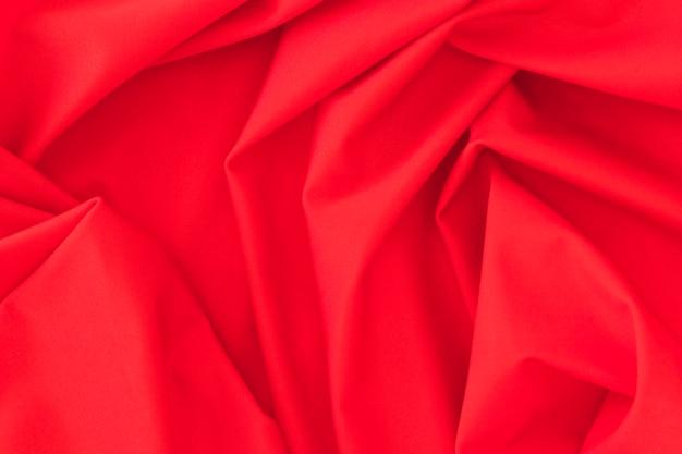De gevouwen rode achtergrond van de textielstoffentextuur