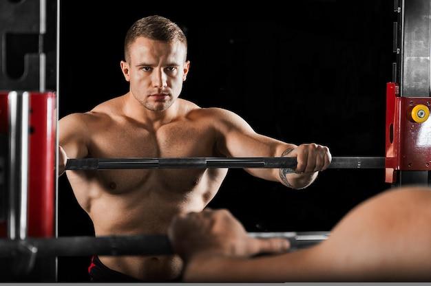 De gewichtheffer houdt zijn handen op de halter en kijkt naar zichzelf in de spiegel. reflectie in de spiegel