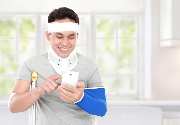 De gewonde jonge mens kijkt gelukkig spelsmartphone