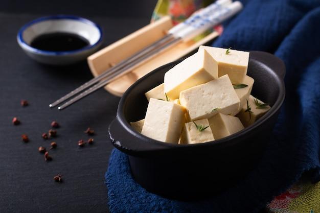 De gezonde aziatische organische tofu van het voedselconcept in zwarte ceramische kop met exemplaarruimte