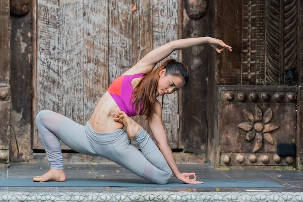 De gezonde aziatische yogavrouw die yoga doen stelt thuis.