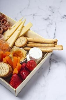De gezonde brunchdoos haalt met ham, aardbeien weg; kiwi; brood; koekjes; kaas, wortelen, mandarijnen, hummus.