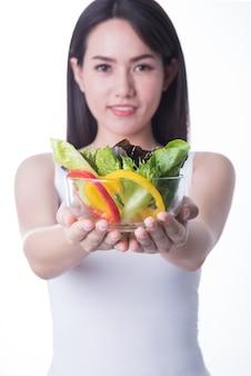 De gezonde die vrouw van azië met salade op witte achtergrond wordt geïsoleerd