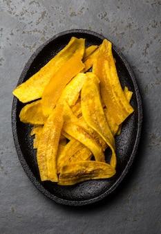 De gezonde eigengemaakte spaanders van de banaanweegbree op zwarte plaat