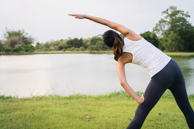 De gezonde jonge aziatische agentvrouw warmt het lichaam op dat zich vóór oefening en yoga uitrekt