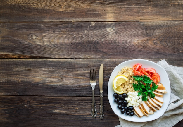 De gezonde kom van kippenquinoa met kersentomaten, feta, olijven en peterselie op rustieke houten oppervlakte. bovenaanzicht met ruimte voor tekst.