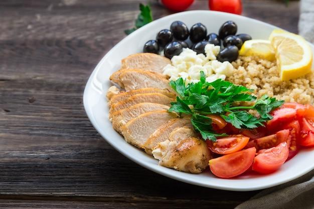De gezonde kom van kippenquinoa met kersentomaten, feta, olijven en peterselie op rustieke houten oppervlakte.