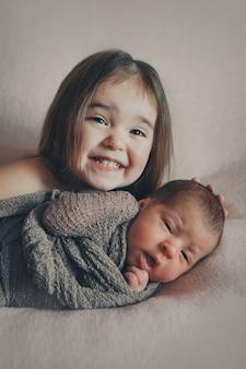 De gezonde levensstijl, de bescherming van kinderen, winkelen voor een kind met een pasgeboren baby die samen speelt.