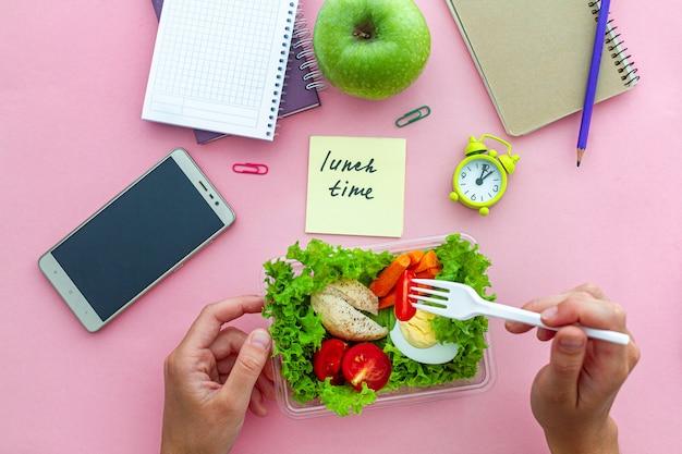 De gezonde organische snack van haalt lunchdoos op het werk tijdens tijdpauze op kantoor weg. container uitgebalanceerd voedsel op het werk. bovenaanzicht