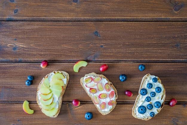 De gezonde sandwiches met fruit, de bosbessen van perzikdruiven en zachte kaas op roze houten achtergrond, hoogste vlakke mening, leggen