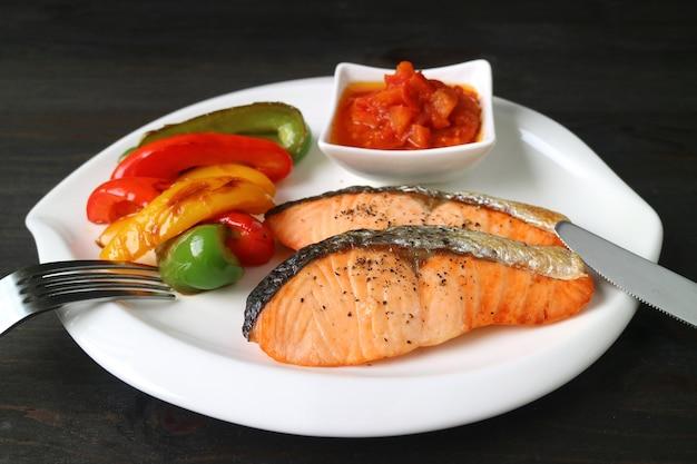 De gezonde schotel van geroosterde zalmlapjes vlees met kleurrijke groenten diende op donkere bruine houten lijst