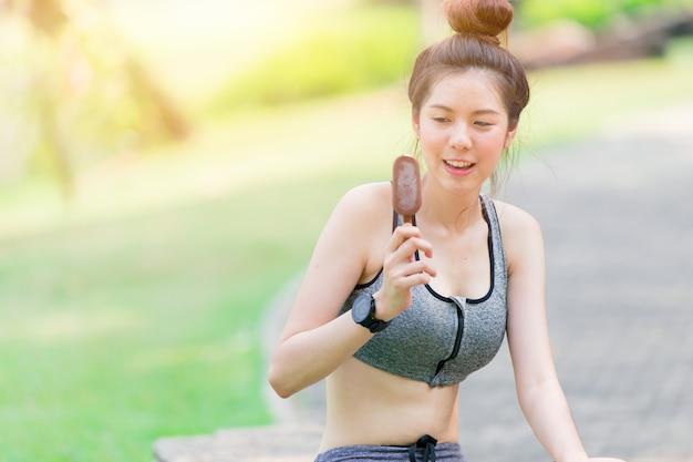 De gezonde tiener van het sport slanke meisje ontspant het eten van chocoladeroomijs na training
