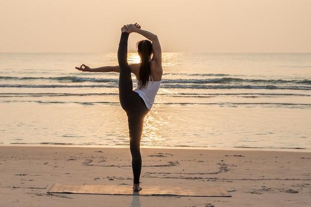 De gezonde vrouw die yoga doet stelt op het strand in de ochtend.